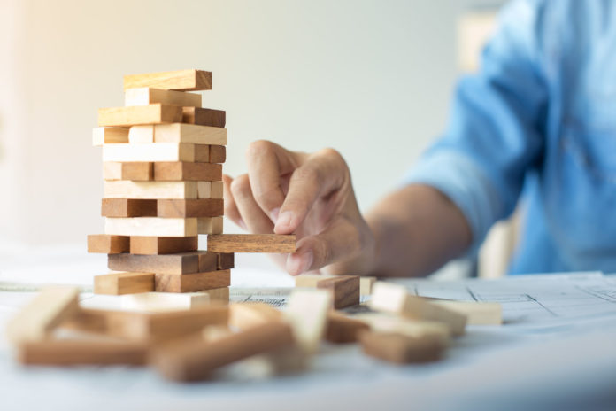 Planning Risk And Strategy In Business Businessman And Engineer Gambling Placing Wooden Block On A Tower