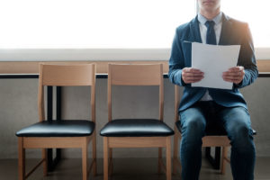Confident Young Businessman Holding Paper While Sitting On A Row Of Chairs Waiting For Interview